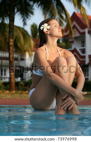 Young woman in swimming pool with flower in hairs - stock photo