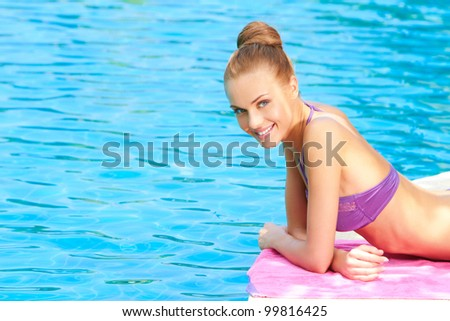Young woman in swimsuit lying close to swimming pool