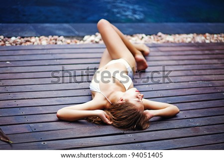 Young woman in swimsuit  lying on the wooden floor outdoors - stock photo