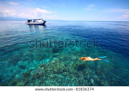 Young woman in swimsuit snorkeling in blue and transparent tropical sea not far away from a boat - stock photo