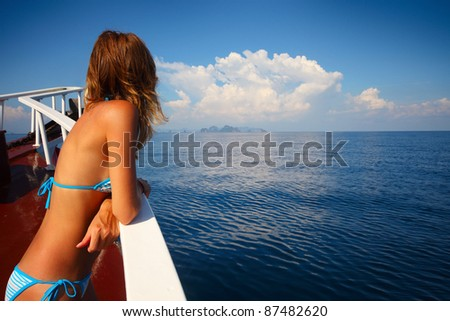 Young woman in swimsuit standing on a shipboard and looking to the sea - stock photo