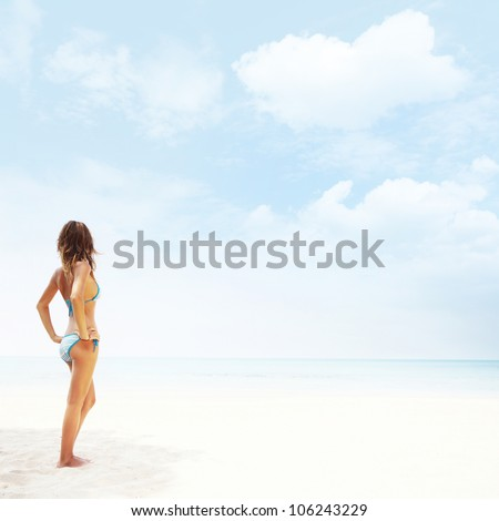Young woman in swimsuit standing on a white sand and looking to a blue clear sky - stock photo
