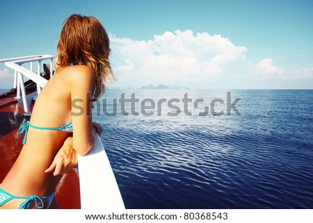 Young woman in swimsuit standing on yacht at sunny day and looking to a sea - stock photo
