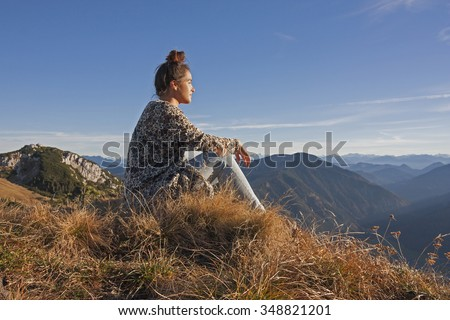 young woman in the bavarian alps, enjoying the evening sun in autumn - stock photo