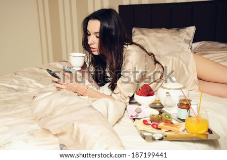 young woman in the bed with phone and breakfast          - stock photo