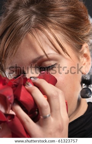 Young woman in the bliss breathe fragrance of rose petals