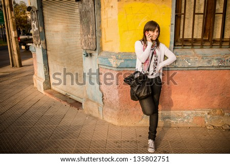Young woman in the city talking on the phone against a wall - stock photo