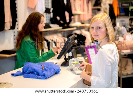 young woman in the clothes shop over the counter - stock photo