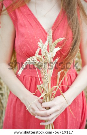young woman in the field holding bundle of the golden wheat ears