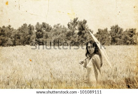 Young woman in the field. Photo in old color image style. - stock photo