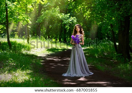 Young woman in the forest (version with sunrays)