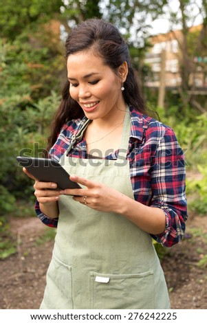 young woman in the garden with her tablet