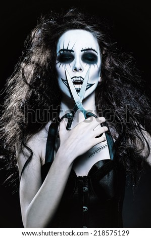 Young woman in the image of a sad gothic freak clown with scissors in hand - stock photo