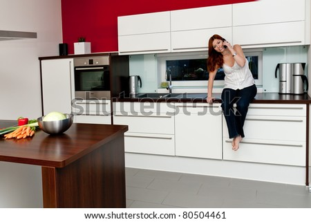 Young woman in the kitchen talking on the phone - stock photo