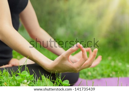 Young woman in the lotus position close up. Yoga meditation at outdoor. Copyspace - stock photo