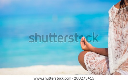Young woman in the lotus posture close up - stock photo