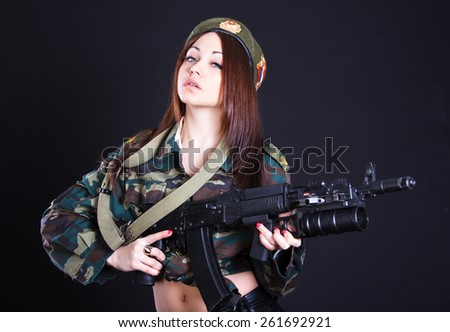 Young woman in the military uniform with the assault rifle over black background - stock photo