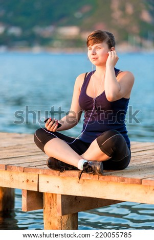 young woman in the morning sun sitting on the pier with the player - stock photo