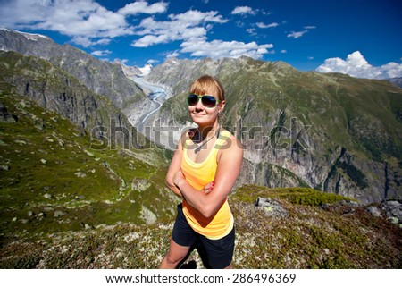 young woman in the mountains against the glacier and blue sky with beautiful clouds. - stock photo