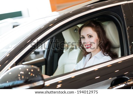 young woman in the new car in the showroom, smiling and looking in camera - stock photo
