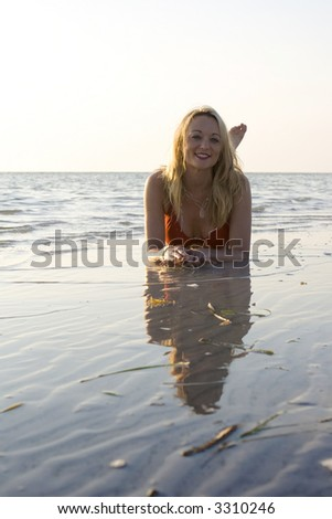 Young woman in the ocean, looking ahead.  Wearing red swimsuit. - stock photo