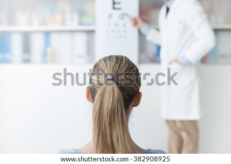 Young woman in the optometrist office examining her eyesight, he is pointing at the chart, eye care concept
