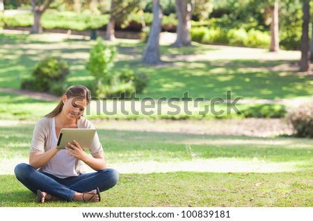 Young woman in the park with a tablet computer - stock photo