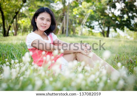 Young woman in the park with flowers. Outdoor portrait