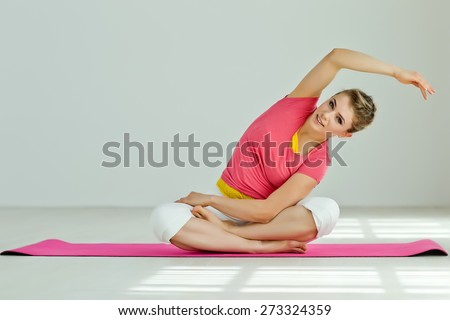 Young woman in the Pigeon yoga pose. Series - stock photo