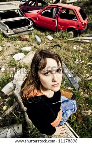 Young woman in the scrapyard - stock photo