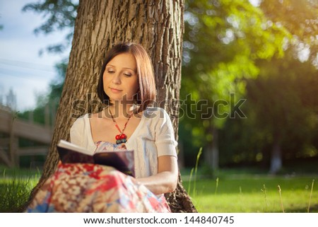 young woman in the shade of a tree reading a book - stock photo