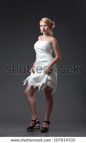 young woman in the short wedding dress on black background - stock photo