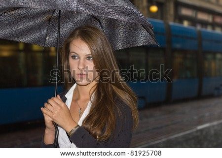 Young woman in the street  during rainy evening - stock photo