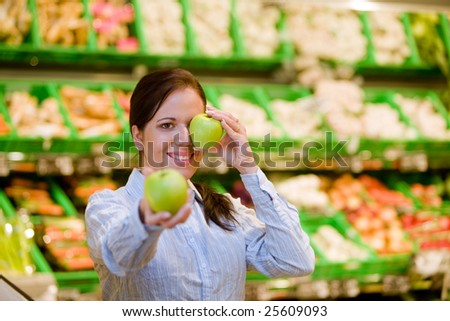 Young woman in the supermarket to buy food and a fruit - stock photo