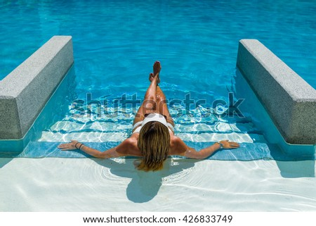 Young woman in the swimming pool at the sesort - stock photo