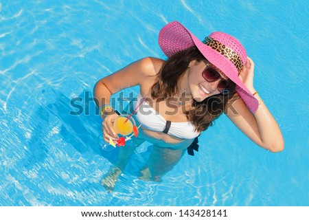 Young woman in the swimming pool holding a cocktail glass
