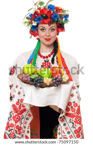Young woman in the Ukrainian national clothes with fruit - stock photo