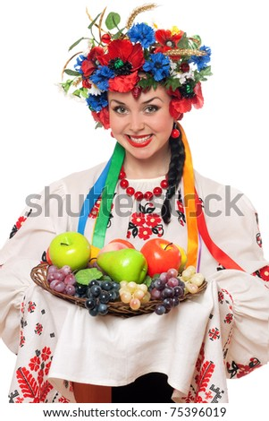 Young woman in the Ukrainian national clothes with fruit. Isolated - stock photo