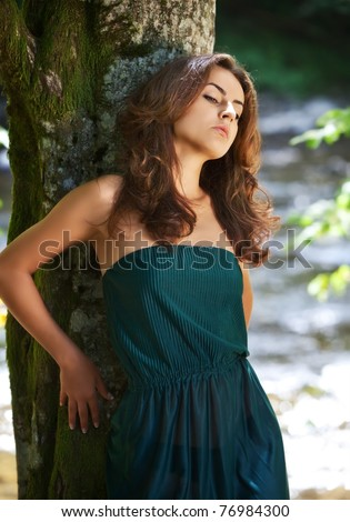 Young woman in the wood near the river - stock photo