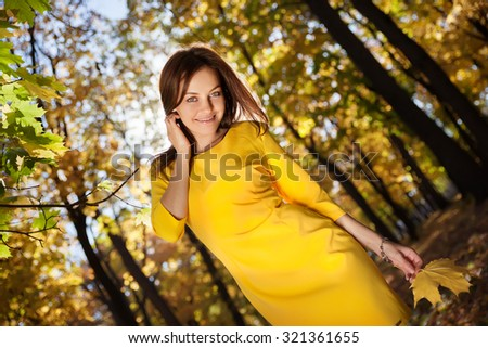 Young woman in the yellow dress with autumn leaves in hand and fall yellow maple garden background - stock photo