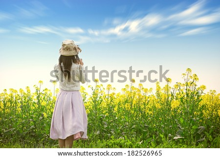 Young woman in the yellow rape field - stock photo