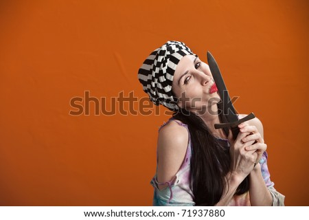 Young woman in tie-dye kisses a dagger - stock photo