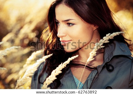 young woman in topcoat portrait at autumn meadow