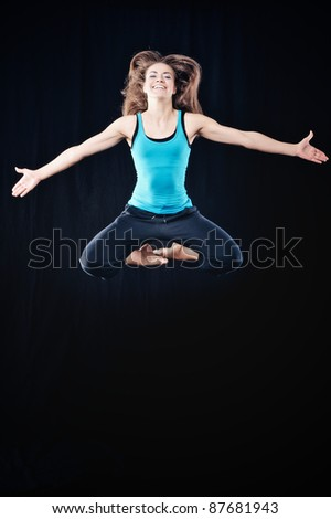 Young woman in tracksuit jumping on black background - stock photo