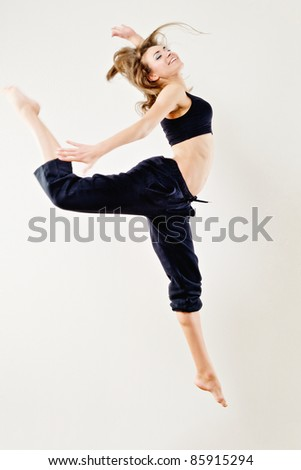Young woman in tracksuit jumping on white background - stock photo