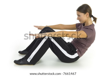 Young woman in tracksuit sitting on the floor and doing some kind of exercise. Isolated on white in studio. Side view, whole body - stock photo