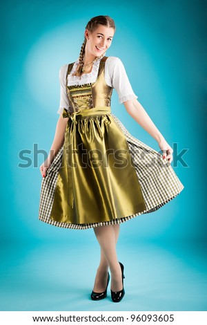 Young woman in traditional Bavarian clothes - dirndl or tracht - studio shoot - stock photo
