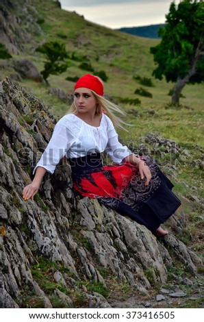 Young woman in traditional costume looking over hill