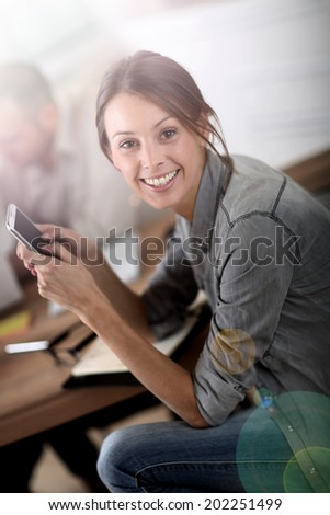 Young woman in training class sending text message
