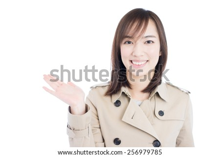 young woman in trench coat showing copy space, isolated on white background - stock photo